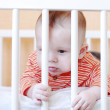 Sad baby in white bed — Stock Photo