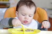Baby eats buckwheat groats — Stock Photo