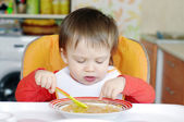 Baby eating soup on kitchen — Stock Photo