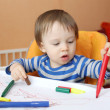 Stock Photo: Baby age of 16 months paints with pens