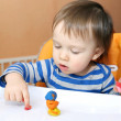 Stock Photo: Baby age of 1 year with plasticine at home