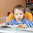 Stock Photo: Baby age of 1 year reading book