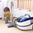 Baby with vacuum cleaner — Stock Photo