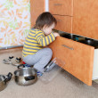 Stock Photo: Curious baby looks into drawer on kitchen