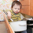 Stock Photo: Baby sitting in drawer on kitchen