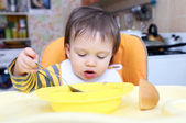 Baby age of 16 months eating soup — Stock Photo