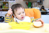 Baby eating soup and bread — Stock Photo