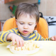 Stock Photo: 16 months baby eating corn curls