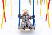Baby on seesaw in winter — Stock Photo