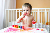 Nice baby with paints — Stock Photo