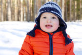 Portrait of happy 18 months baby in winter forest — Stock Photo