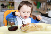 Baby eats pancakes with jam — Stock Photo