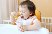 18 months baby eats youghourt — Stock Photo