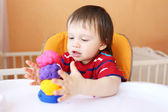 Lovely baby with plasticine at home — Stock Photo