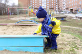 Baby playing with sand on playground in spring — Stock Photo