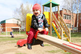 Happy 18 months baby on seesaw outdoors — Stock Photo