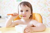 Happy lovely baby eating fruity puree — Stock Photo