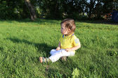 Baby sitting on grass in summer — Stock Photo