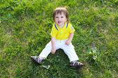 Lovely baby boy sitting on grass in summer — Stock Photo