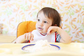 Wistful baby eating quark — Stock Photo