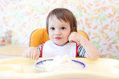 Happy baby eating quark — Stock Photo