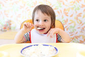 Happy baby boy eating quark — Stock Photo