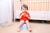 Baby sitting on potty and eating biscuit — Stock Photo