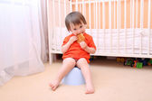 Baby boy sitting on potty and eating biscuit — Stock Photo