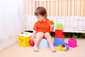 Baby plays toys sitting on potty — Stock Photo