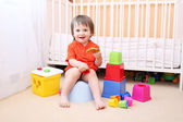 Baby with toys and waffle sitting on potty — Stock Photo