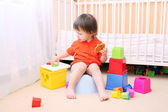 Lovely baby plays toys sitting on potty — Stock Photo