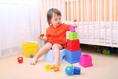 Baby boy plays toys sitting on potty — Stock Photo