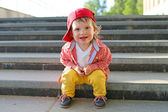 Stylish baby sitting on stairs in summer — Stock Photo