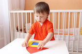 Baby boy constructing house of paper details — Foto Stock