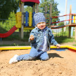 Happy little boy playing with sand on playground — Stock Photo #51188573