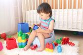 Adorável menino joga brinquedos sentado no penico — Foto Stock