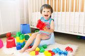 Lindo bebê com brinquedos sentado no penico — Foto Stock