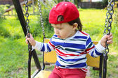 Sad baby boy on swing — Stockfoto