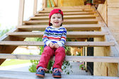 Smiling baby sitting on stairs outdoors — Stock Photo