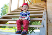 Happy baby sitting on stairs outdoors — Stock Photo