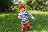 Happy baby running with blowball — Stock Photo