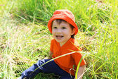 Happy baby in orange hat sitting on grass — Stock Photo