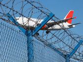 Landing airplane behind barbed wire — Stock Photo