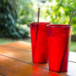 Cold drinking water and ice in the red glass on wooden table — Stock Photo