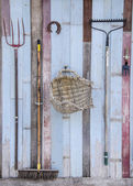 Farmers tools on old wooden barn wall background — Stock Photo