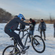 Cyclist moves down from snowy mountains — Stock Photo #37448363