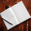 Open a blank white notebook and pen on wood background — Stock Photo