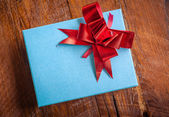 Blue gift box with red ribbon on wood for vintage — Stock Photo