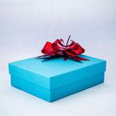 Scatola regalo blu con nastro rosso su sfondo bianco isolato — Foto Stock