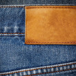 Old jeans texture with leather label background close up — Stock Photo